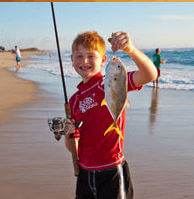 Child angler holding up a fish he caught on a Cape Hatteras beach.